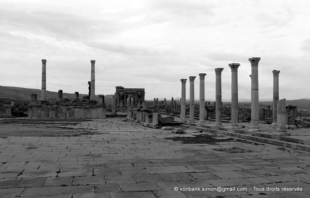 [NB042-1978-24] Timgad (Thamugadi) : Forum - Face Ouest : Temple de Trajan, en arrière-plan Arc de Trajan, Front Nord : Colonnade