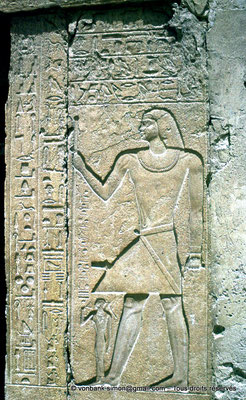 [087-1973-04] Saqqara - Mastaba de Mererouka : (Côté droit de l'entrée) Mererouka debout, sceptre Sekhem de puissance dans une main, grande canne de fonction dans l'autre - Devant lui, mais à une échelle bien inférieure, son épouse Watekhethor