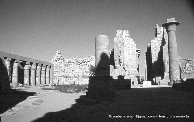 [088-1973-29] Karnak - Grande cour : Portique Nord constitué de 18 colonnes papyriformes fermées dépourvues d'inscription (Chechonq Ier) touchant le môle Nord du pylône II - Porte du pylône II - Colonnes du kiosque de Taharqa