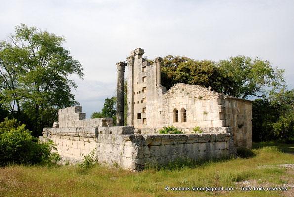 [NU001b-2018-0011] Vernègues (Alvernicum) : Murs de soubassement de la cella - Colonne cannelée et pilastre lisse surmontés de chapiteaux à feuilles d'acanthe - En arrière-plan, la chapelle Saint-Cézaire