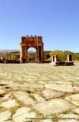 [001-1983-01] Djemila (Cuicul) : Place des Sévères (Nouveau forum) - Arc de Caracalla (vue prise depuis le pied de l'escalier du temple septimien)