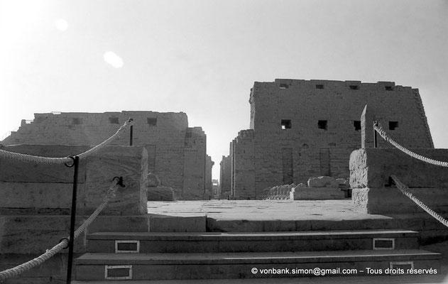 [NB077-1973-02] Karnak - Parvis du Temple : Accès au dromos précédant le premier pylône (môles Nord et Sud) - En arrière-plan, les colonnes de l'allée principale de la salle hypostyle