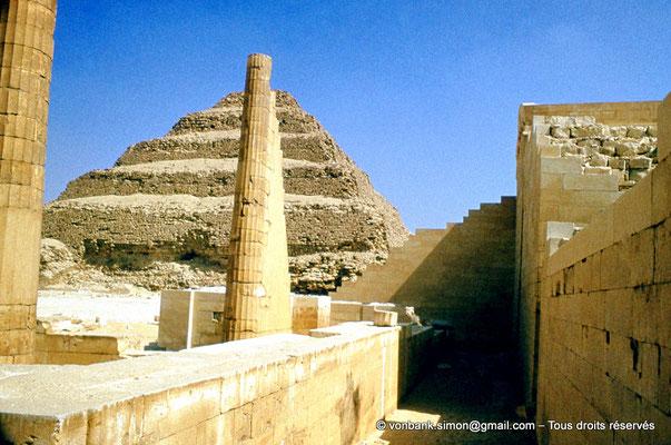 """[083-1973-02] Saqqara - Djoser : Colonnes cannelées du Temple """"T"""" - En arrière-plan, la pyramide à degrés du roi"""