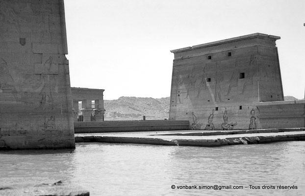 [NB076-1973-49] Philae : Temple d'Isis (parties supérieures de la façade Ouest) - Pylône 2, toit du Mammisi (au ras de l'eau), Kiosque de Trajan, Pylône 1
