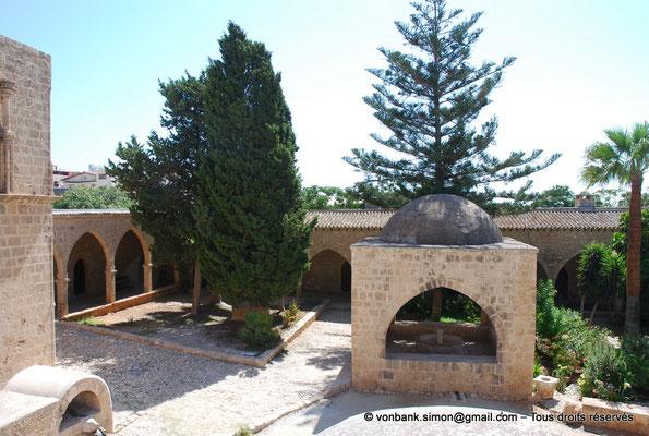 [NU900-2012-0172] Agia Napa : Fontaine octogonale surmontée d'un dôme de pierre (XVI°) - en arrière-plan, galerie extérieure à arcades du monastère (vue partielle)