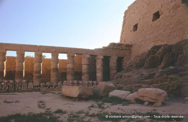 [082-1973-02] Karnak - Grande cour : Colonnade (Chechonq Ier) et rangée de sphinx à tête de bélier (Ramsès II)