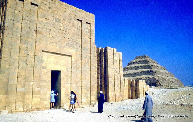[083-1973-07] Saqqara - Djoser : Unique entrée dans le mur d'enceinte de calcaire à bastions et à redans du complexe funéraire - En arrière-plan, la pyramide à degrés du roi