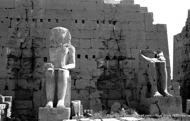 [NB070-1973-14] Karnak - Propylées du Sud : Statues d'Aménophis Ier et de Thoutmôsis II (Môle Ouest, Face Sud du pylône VIII) - En arrière-plan, les pierres éclatées rappellent les deux encoches verticales des mâts à oriflammes