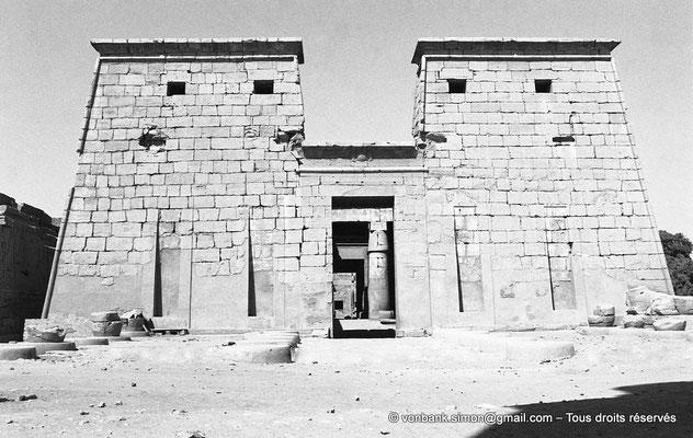 [NB087-1973-04] Karnak - Temple de Khonsou : Façade du temple (premier pylône (haut de 16 mètres)) - En avant, bases des colonnes de Taharqa