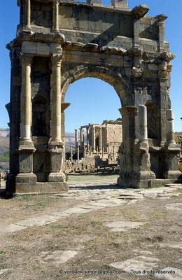 [001-1983-03] Djemila (Cuicul) : Arc de Caracalla - Façade Ouest - En arrière-plan, le Temple Septimien