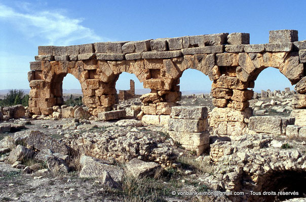 [006-1983-31] Henchir Mdeïna (Althiburos) : Théâtre - Détail du mur périphérique et des 5 travées de son niveau supérieur - En arrière-plan, aperçu du Capitole