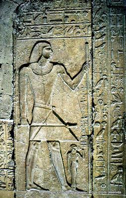 [087-1973-30] Saqqara - Mastaba de Mererouka : (Côté gauche de l'entrée) Mererouka debout, sceptre Sekhem de puissance dans une main, grande canne de fonction dans l'autre - Devant lui, mais à une échelle bien inférieure, son épouse Watekhethor
