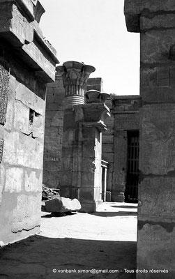[NB087-1973-73] Karnak - Temple de Ptah : Depuis la Porte D, vue sur le montant gauche de la Porte E avec sa colonne composite - En arrière-plan, partie gauche de la Porte F