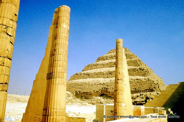 """[083-1973-05] Saqqara - Djoser : Colonnes cannelées du Temple """"T"""" - En arrière-plan, la pyramide à degrés du roi"""