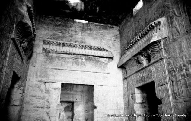 [NB070-1973-68] Karnak - Temple d'Opet : Salle centrale - Portes d'accès au Sanctuaire, à la Salle Nord (à gauche) et à la Salle Sud (à droite) - Disque solaire surmonté d'une frise d'uraeus