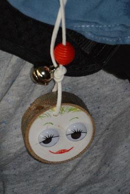 Waldgeistkette: Eine Kette mit einer Baumscheibe mit einem aufgemalten lachendem Gesicht, einer kleinen Glocke und einer roten Perle.