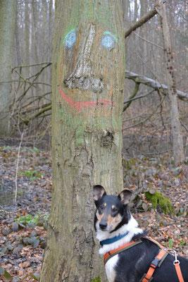 """Blade steht vor Waldgeist """"Flammi"""", der ein Baumstamm ist, auf dem ein lachendes Gesicht aufgemalt ist."""