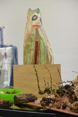 """Waldgeist """"Basti"""" ist ein großes Holzstück, auf dem ein Gesicht aufgemalt ist, an ihm ist ein Bleistift angebracht. Vor """"Basti"""" liegt ein Briefumschlag mit seinem Namen und verschiedene Gegenstände aus dem Wald (Zapfen, Rindenstücke, Holzstücke)."""