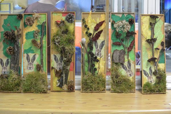 Die Schülerinnen und Schüler haben aus den Waldmaterialien sechs Fühlbilder gebastelt. Dafür wurden Moos, Blatter, Rindenstücke, Holzstücke, Zapfen und andere Dinge auf Holzrahmen geklebt. Auf jedem Bild ist außerdem ein Bild eines Hasenkopfes aufgeklebt.