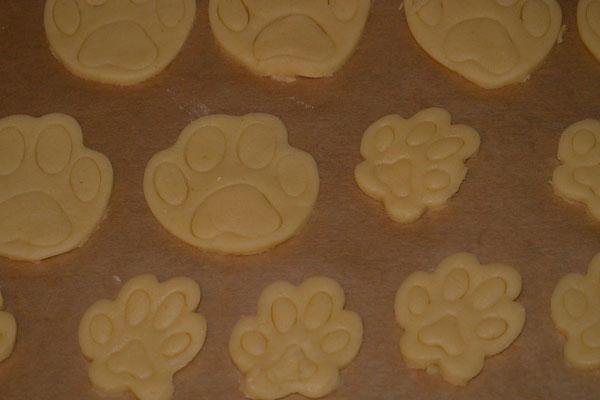Kekse in Form von kleinen und großen Pfotenabdrücken auf einem Blech (Nahaufnahme)