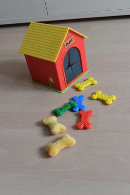 Eine sehr kleine Plastik-Hundehütte mit einem Eingriff für die Hand. Dazu gehören Plastik- und Stoffknochen mit unterschiedlichen Oberflächen, z.B. weich, glatt, knubbelig etc. Immer zwei sind gleich.