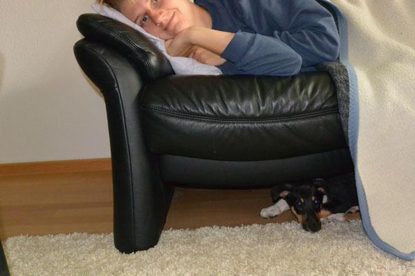 Mittagsschlaf (8 Wochen alt) Frauchen liegt auf dem Sofa, Blade darunter.