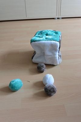 Ein Würfel aus Plüsch mit Eingriffen an jeder Seite, dazu gehören vier Plüschbälle, die geworfen oder im Würfel versteckt werden können.