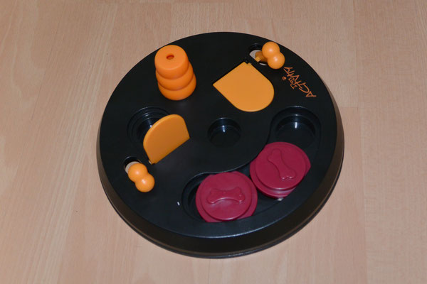 Eine Plastikscheibe mit Löchern auf der Oberseite, die auf unterschiedliche Art geöffnet bzw. geschlossen werden können, z.B. durch Verschieben eines Plättchens oder durch Betätigen eines kleinen Hebels. In den Löchern kann Futter versteckt werden.