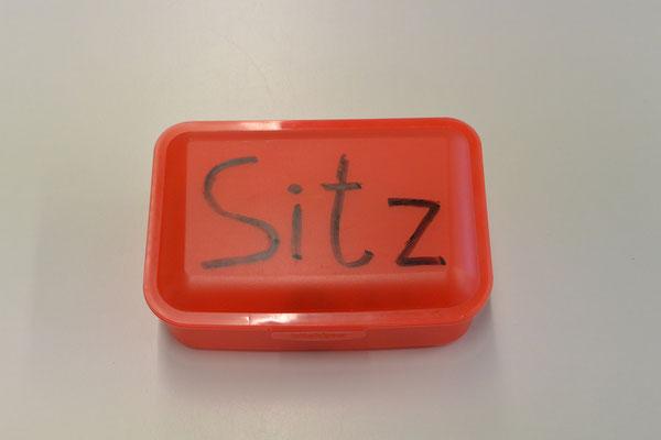 """Eine Brotdose mit der Aufschrift """"Sitz"""". Zeigt man Blade die Box, setzt er sich hin."""