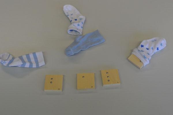 Auf dem Tisch liegen Holzklötzchen, auf denen mit Nägeln die Punktschriftbuchstaben b, a und l dargestellt sind. Daneben liegen Socken, in einem Socken sieht man einen weiteren Holzklotz stecken.