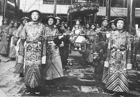 241. — S. M. l'Impératrice Tseu-hi dans sa chaise à porteurs, entourée du grand eunuque Li Lien Jing et de son premier lieutenant.