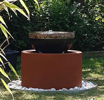 GFK Becken ø ca- 65 cm mit GFK Schürze in Rostoptik verkleidet. Das Becken könnte auch ein Stück eingegraben werden. Quellstein ø 50 cm Dekor Schiefer