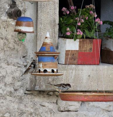 Vogeltränke zum Hängen, Dekor Granatapfel, ø ca. 28,5 cm, h ca. 4,5 cm, dahinter Vogelfutterhaus klein und Meisenglocke Dekor Santorin, Blumenkasten Dekor Granatapfel