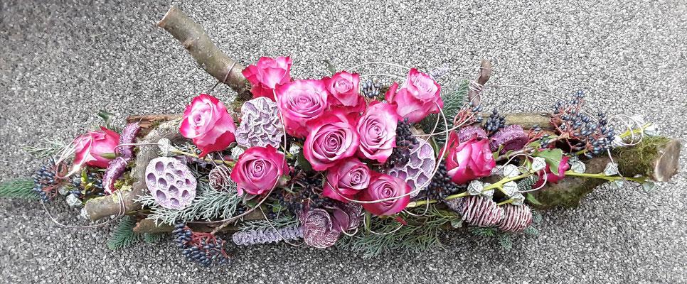 Längliches Gesteck mit lila Rosen auf Geäst