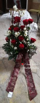 Gesteck mit roten Rosen und weißen Christrosen