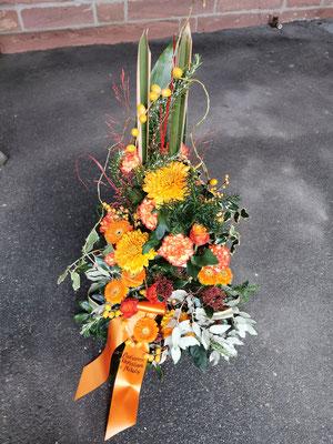 Trauergesteck orange Schleife