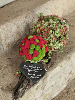 Gesteck mit Blütenkugeln aus Hortensien und Rosen mit Schiefertafel auf Rindenstück