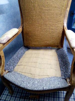 Une toile forte est fixée sur les traverses. Les ressorts sont cousus pour consolider l'assise. Des profilés viendront donner la forme de l'assise. Une mousse y sera collée.