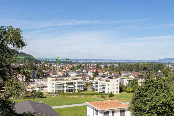 Blick zum Wohnerlebnis SunneThal und zum Bodensee. Auf den Dächern befinden sich Solaranlagen. Die Balkonbrüstungen aus satiniertem Glas sind lichtdurchlässig und dienen als Wind- und Sichtschutz
