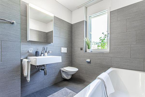 Hochwertige Feinsteinzeugplatten in den beiden Tageslicht-Badezimmern