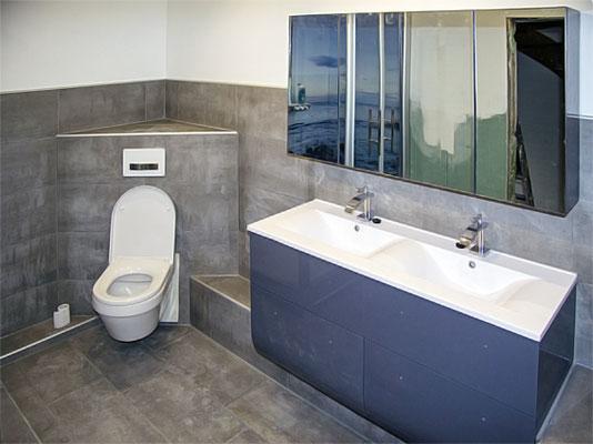 Blick in ein Badezimmers in Beton Optik, bei der die Wand mit Mikrozement bearbeitet wurde.