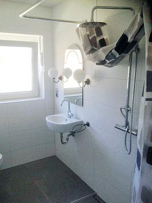 Ansicht seitlich in  ein weißes, renoviertes Badezimmer.