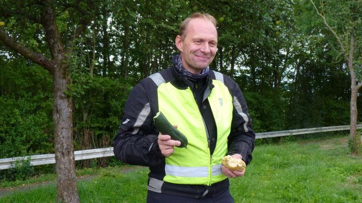 Lars genießt eine frische Gurke aus seinem Garten zum zweiten Frühstück