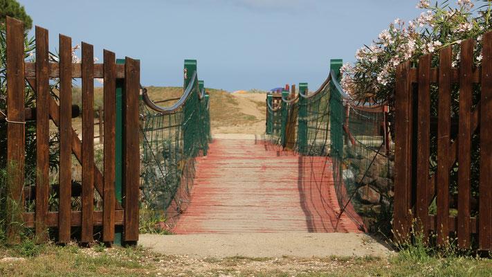 Vom Stellplatz führt eine Hängebrücke über einen flachen Wasserarmdie Lagune direkt an den feinen Sandstrand