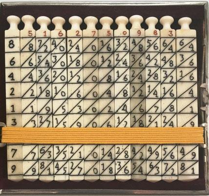 Ábaco multiplicativo de NAPIER, 12 varillas cuadrangulares (11 de 0.6X7 cm y 1 de 0.8x7 cm). Diseño: diagonal principal, desordenado: centro impares ascendente hacia abajo, con indicador de las 4 caras de cada varilla