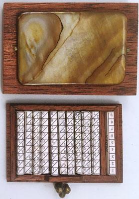 Miniatura de huesos de Napier: caja con piedra de adorno y conjunto de 11 varillas cuadrangulares de 0.2x2 cm cada una, año 2010