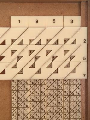 Ejemplo de producto 1953x257=501921. El multiplicando se forma con las varillas numéricas 1,9,5,3 y sobre ellas se colocan las tres varillas lectoras 2,5,7 del multiplicador. El resultado se obtiene sumando las diagonales, de derecha a izquierda