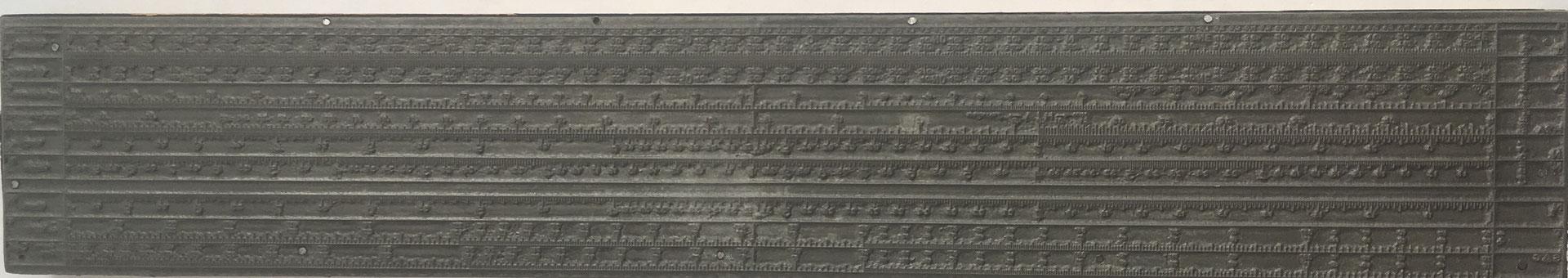 Cliché (matriz o plancha) de metal sobre base de madera para máquina plana de la Regla Universal Tipográfica CONDE (modelo 2), 43.5x7.5 cm