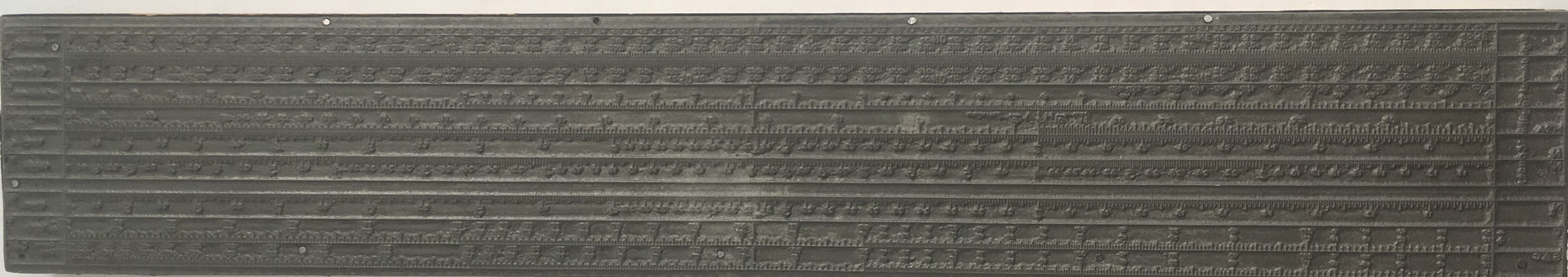 Cliché (matriz o plancha de imprenta) hecho en metal sobre base de madera para máquina plana de la Regla Universal Tipográfica CONDE (modelo 2), 43.5x7.5 cm