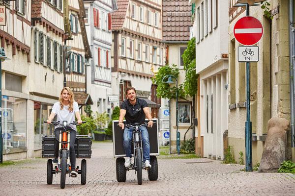 Frau und Mann fahren mit den Transporträdern von XCYC durch die Stadt